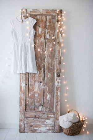 wooden floors: Summer dress, vintage wooden door, basket and decorative lights, girls room interior decoration with white walls and floors.