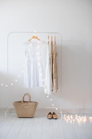 Vestido de verano, puerta de madera vintage, cesta y luces decorativas, sitio de las muchachas de la decoración interior con paredes blancas y suelos.