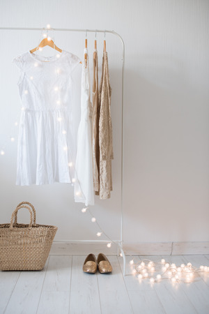 Summer dress, vintage wooden door, basket and decorative lights, girls room interior decoration with white walls and floors.