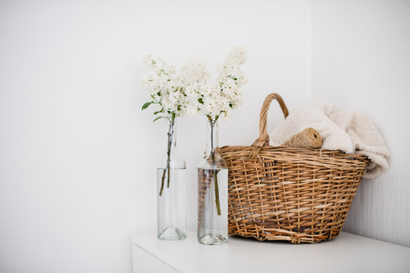 Wicker basket with home textiles and white lilac on a white chest, white vintage room interior decoration.