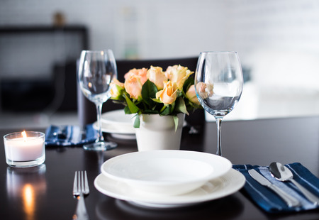 plate setting: Simple home table setting, glasses and cutlery, roses in a vase.