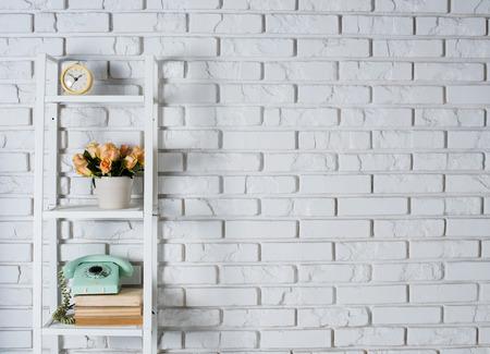 ビンテージ調の装飾、白いレンガの壁の前に室内装飾棚
