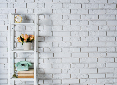 room decorations: Shelf with interior decoration in front of a white brick wall, vintage decor