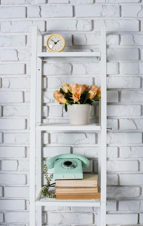 Estante con decoración interior delante de una pared de ladrillo blanco, del vintage Foto de archivo
