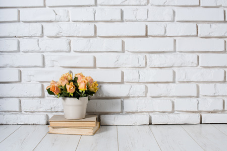 Roses in a vase and a stack of old vintage books on a  white brick wall background, room interior.