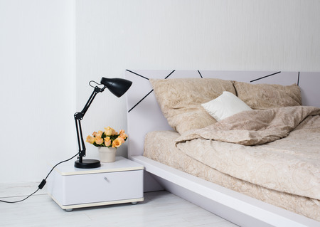Bright white bedroom interior, cozy bed with beige linen, flowers on a bedside table. photo