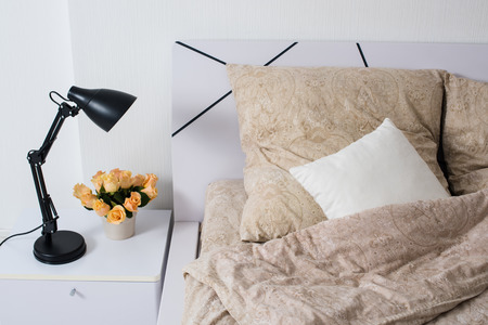 Bright white bedroom interior, cozy bed with beige linen, flowers on a bedside table, closeup photo