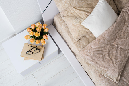 Bright white bedroom interior, cozy bed with beige linen, flowers on a bedside table, shot from above.