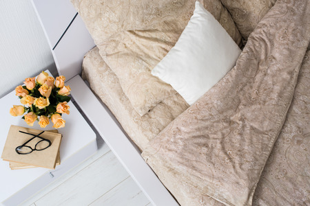 ベージュのリネン、ベッドサイドのテーブルの上の花と明るい白い寝室インテリア、居心地の良いベッドを上から撮影。