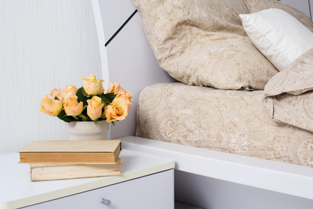 bedside: Bright white bedroom interior, cozy bed with beige linen, flowers on a bedside table, closeup Stock Photo