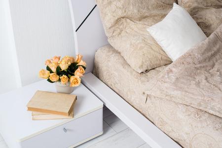 Яркий белый интерьер спальни, уютная кровать с бежевым белья, цветы на тумбочке, крупным планом