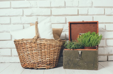 wall decoration: Wicker basket with a pillow and green home plant at the white brick wall on the floor, rustic home interior decor