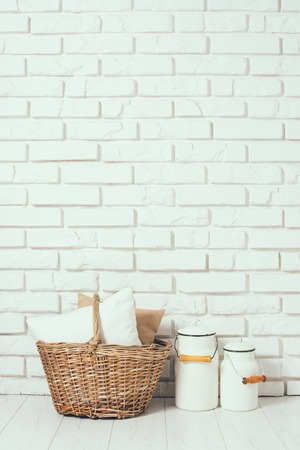 milk cans: Wicker basket with a pillow and milk cans at the white brick wall on the floor, rustic home interior decor