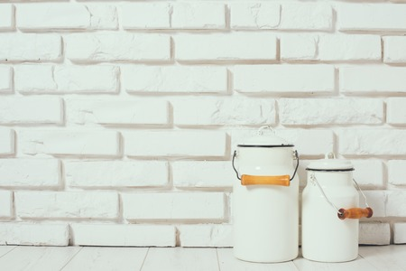 Milk cans at the white brick wall on the floor, rustic home interior decor