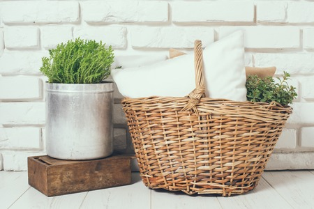 Wicker basket with a pillow and green home plant at the white brick wall on the floor, rustic home interior decor