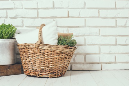 Wicker basket with a pillow and green home plant at the white brick wall on the floor, rustic home interior decor with copy space