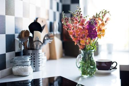 Bosje verse zomerbloemen in een kruik in het interieur van de moderne keuken, close-up