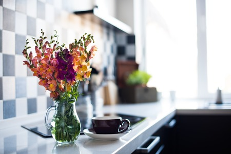 glass vase: Bunch of fresh summer flowers in a jug in home interior of modern kitchen, close-up