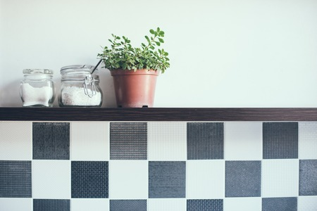 Domestic plant in a pot and jars on the kitchen shelf on the wall, close-up Stock fotó