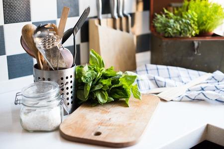 sal: Un manojo de albahaca en la placa sobre la mesa de la cocina, utensilios de cocina en casa para cocinar.