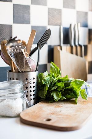 albahaca: Un manojo de albahaca en la placa sobre la mesa de la cocina, utensilios de cocina en casa para cocinar.