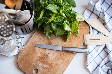 A bunch of basil on the board on the kitchen table, home cooking utensils for cooking, top view photo