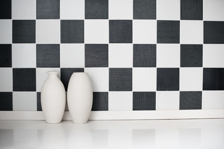 ceramic bottle: Two ceramic vases on a table near the black-and-white wall