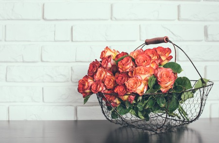 A bouquet of roses in a basket on a shelf near the white brick wall photo