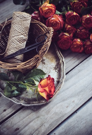 floristic: Floristic background, a bouquet of roses, scissors and twine in a basket on an old vintage wooden board. Stock Photo