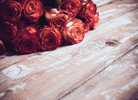 A large bouquet of fresh roses on an old wooden board, vintage background