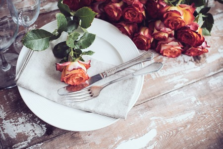 plate setting: Vintage table setting with glasses and cutlery on an old wooden board, wedding table decor