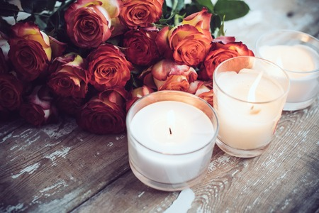 candles: Vintage holiday decor, a bouquet of red roses and burning candles on an old wooden board surface, wedding decoration