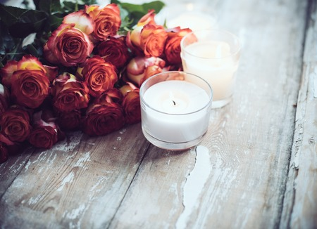 Vintage holiday decor, a bouquet of red roses and burning candles on an old wooden board surface, wedding decoration photo