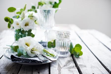오래된 빈티지 소박한 나무 테이블에 흰색 꽃, 촛불, 안경 테이블 설정. 빈티지 여름 웨딩 테이블 장식. 스톡 콘텐츠