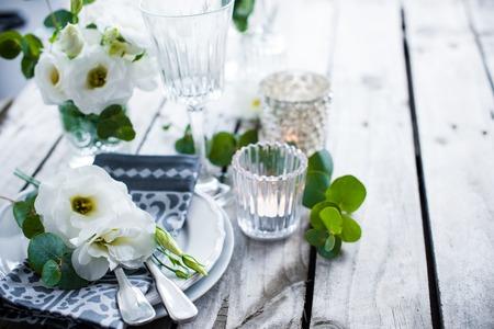 白い花、蝋燭、古いビンテージ素朴な木製のテーブルにガラス テーブルの設定。ビンテージの夏結婚式のテーブル デコレーション。