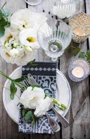 Сервировка стола с белыми цветами, свечами и очках на старой марочное деревенский деревянный стол. Урожай летом свадьба украшение стола, вид сверху. Фото со стока