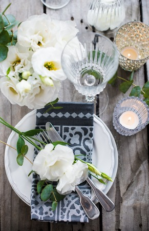 白い花、蝋燭、古いビンテージ素朴な木製のテーブルにガラス テーブルの設定。ビンテージ夏結婚式のテーブルの装飾、平面図。