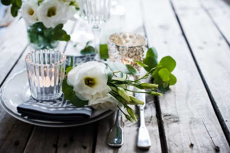 Table setting with white flowers, candles and glasses on old vintage rustic wooden table. Vintage summer wedding table decoration.