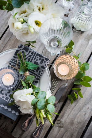 Table setting with white flowers, candles and glasses on old vintage rustic wooden table. Vintage summer wedding table decoration, top view. Stock Photo