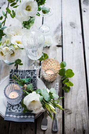 wedding table decor: Table setting with white flowers, candles and glasses on old vintage rustic wooden table. Vintage summer wedding table decoration.