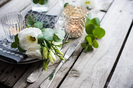 Table decor with white flowers, candles and glasses on old vintage rustic wooden table. Vintage summer wedding table decoration.