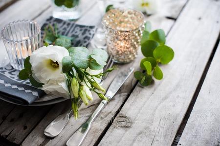 Tafel decor met witte bloemen, kaarsen en een bril op oude vintage rustieke houten tafel. Vintage zomer bruiloft tafeldecoratie.