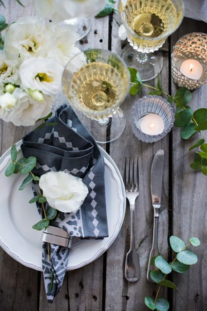 Glasses of champagne and candles: Table setting with white flowers, candles and glasses of champagne on an old vintage rustic wooden table. Vintage summer wedding table decoration, top view. Kho ảnh