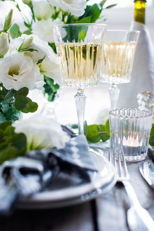 Glasses of champagne and candles: Table setting with white flowers, candles and glasses of champagne on an old vintage rustic wooden table. Vintage summer wedding table decoration. Kho ảnh