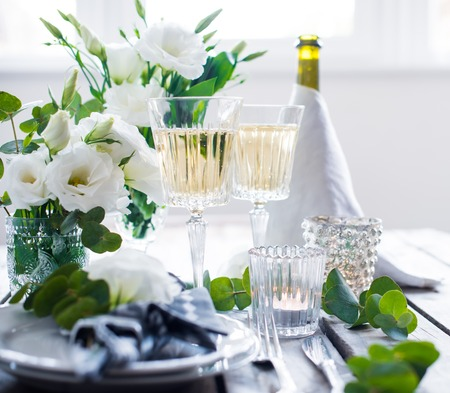 dinner party: Table setting with white flowers, candles and glasses of champagne on an old vintage rustic wooden table. Vintage summer wedding table decoration. Stock Photo