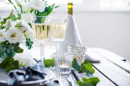 setting: Table setting with white flowers, candles and glasses of champagne on an old vintage rustic wooden table. Vintage summer wedding table decoration. Stock Photo