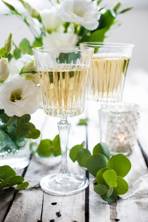 crystal glass: Two glasses of champagne and white flowers, candles on an old vintage rustic wooden table. Vintage summer wedding table decoration. Festive decor. Stock Photo