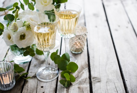 crystal glass: Two glasses of champagne and white flowers, candles on an old vintage rustic wooden table.