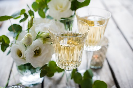 Glasses of champagne and candles: Two glasses of champagne and white flowers, candles on an old vintage rustic wooden table.