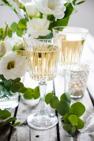 Glasses of champagne and candles: Two glasses of champagne and white flowers, candles on an old vintage rustic wooden table. Vintage summer wedding table decoration. Festive decor. Kho ảnh